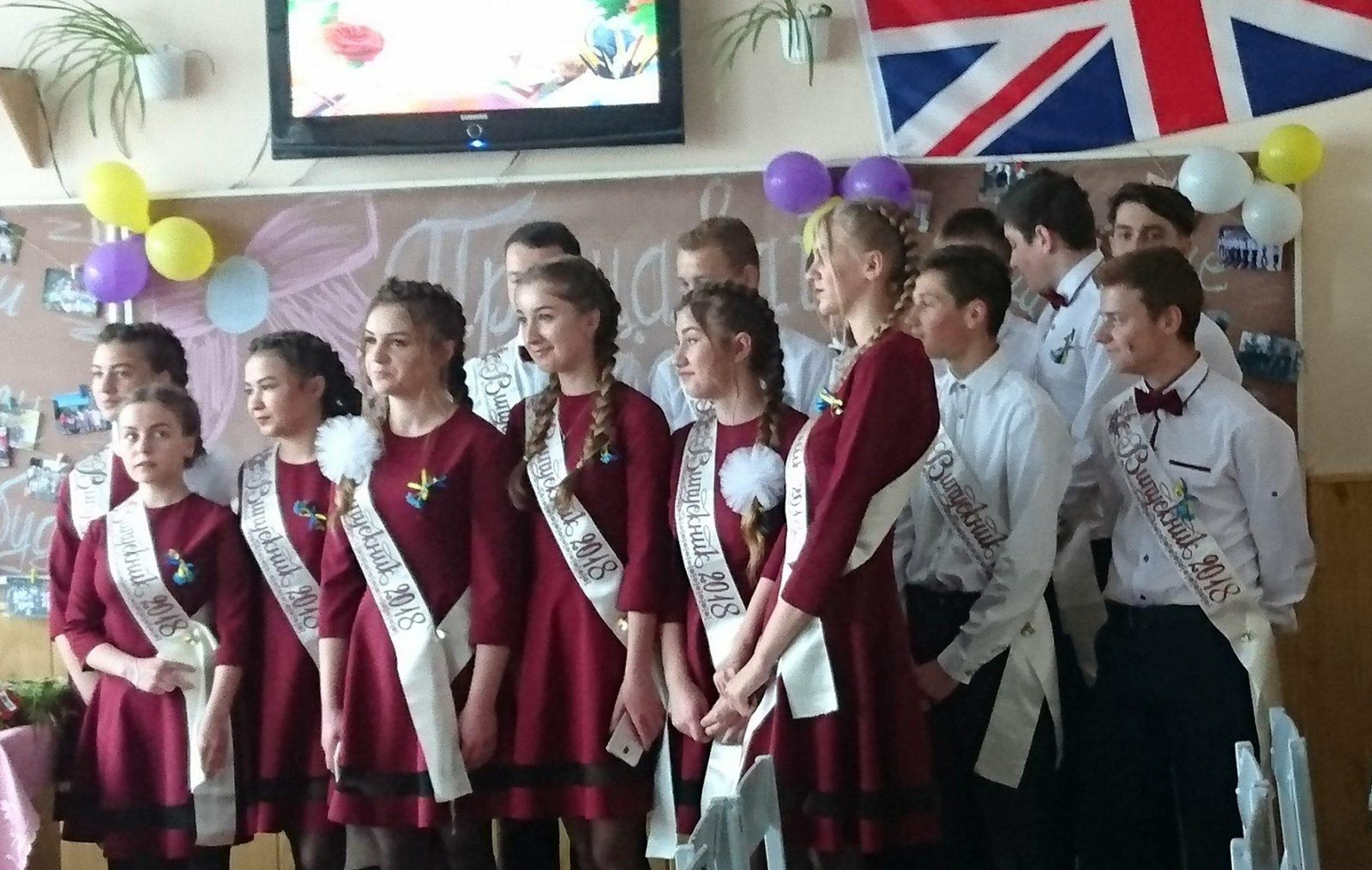 Seniors from the local school sing a song of thanks to their teacher. The Union Jack is an important symbol for them too, as they are the first class which has had English classes since the third class. Photo: Michael V. Owens