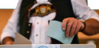 A voter in traditional Bavarian attire casts his ballot at a polling station in Irschenberg ( EPA/PHILIPP GUELLAND )
