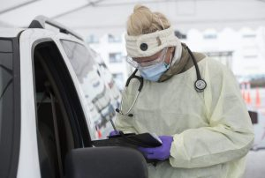 U.S. Air Force Staff Sgt. Maxime Copley, 86th Medical Group independent duty medical technician, writes down patient information in the Ramstein Medical Clinic's coronavirus disease 2019 screening drive-thru at Ramstein Air Base, Germany, March 31, 2020. The 86th MDG transformed their main parking lot into a drive-thru to expedite testing and prevent the spread of COVID-19. (U.S. Air Force photo by Airman 1st Class Taylor D. Slater)